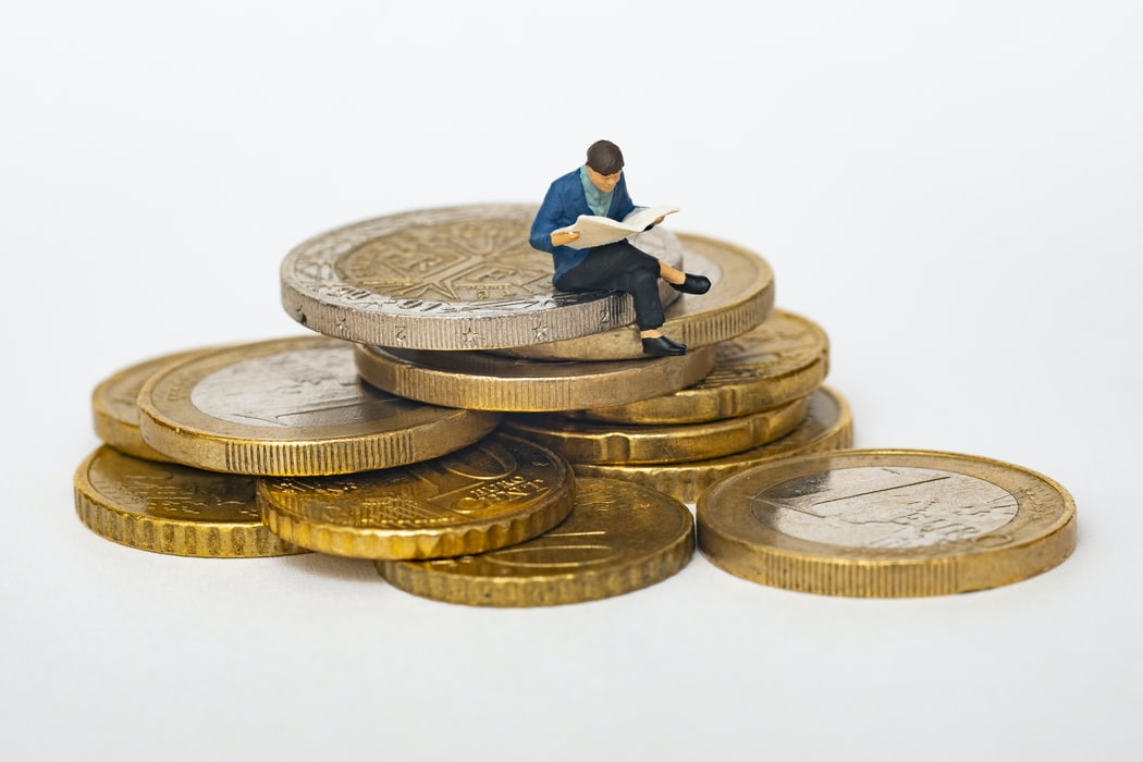 Little man s sitting on coins