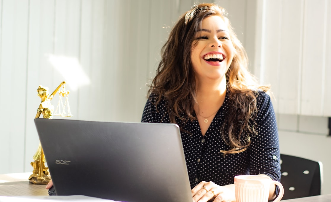 woman laughing in front of laptop